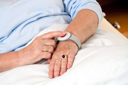 panic button: help a senior citizen with emergency phone call in bed