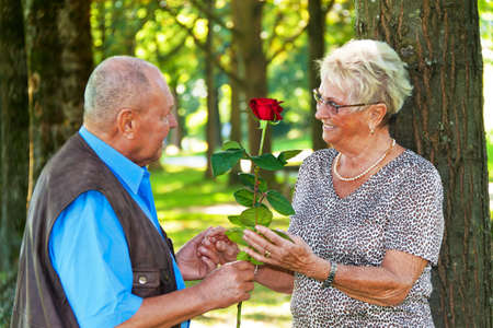 few: older elderly couple in love  man gives a rose