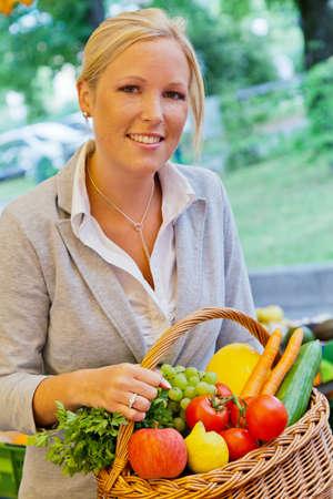 canastas con frutas: una joven mujer compra frutas y verduras en un mercado de alimentos frescos y saludables