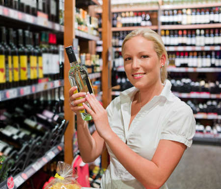 a woman buys wine in a supermarket  wine rack with wines from around the world  photo