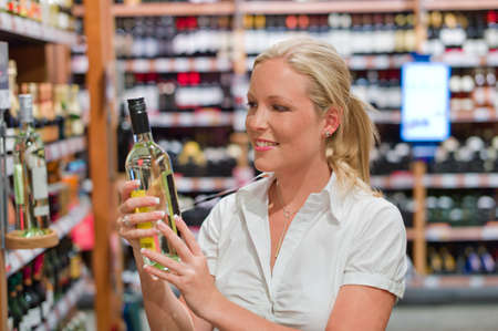 local supply: a woman buys wine in a supermarket  wine rack with wines from around the world  Stock Photo