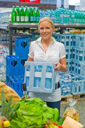 a young woman buys bottled water in the beverage department at the supermarket  Stock Photo - 14488886