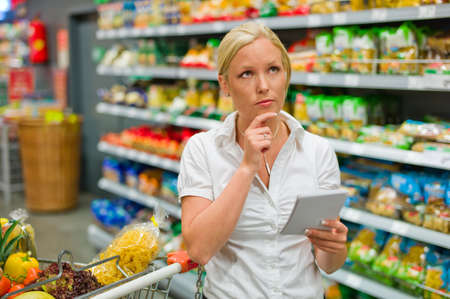 grocer: a woman is overwhelmed by the huge selection when shopping in a supermarket  Stock Photo