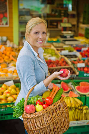 a young woman buys fruits and vegetables at a market  fresh and healthy food  photo
