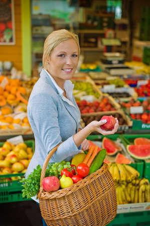 köylü: genç bir kadın bir pazar taze ve sağlıklı gıda olarak meyve ve sebze satın alır Stok Fotoğraf