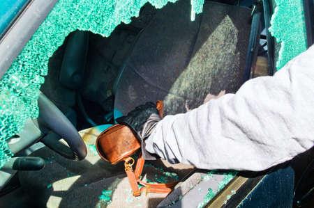 eingeschifft: ein Dieb stahl eine Handtasche aus einem Auto durch eine zerbrochene Seitenscheibe Editorial