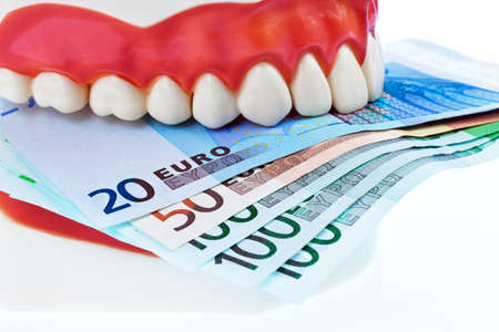 surgery expenses: a tooth model at the dentist with euro notes  costs for health  Stock Photo