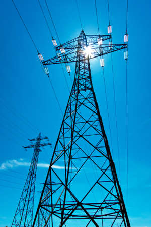 the utility pole of a high voltage line with the sun and blue sky  energy supply from power line  photo