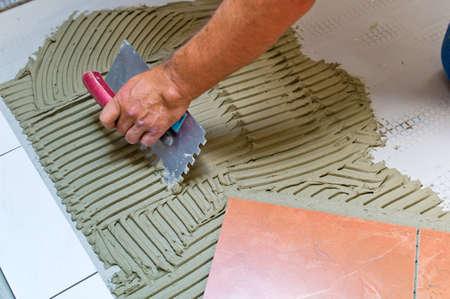 tegelwerk: een tegelzetter aan het werk verlijmen van tegels met tegellijm en vulmiddel