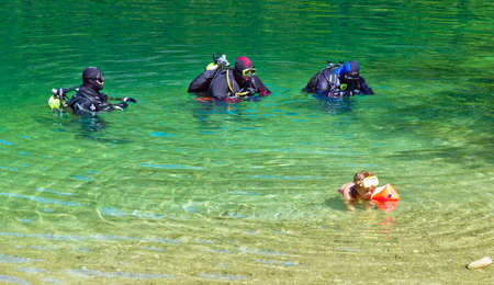 freetime activity: in a sea divers get ready for a dive  austria, upper austria, langbathsee  Editorial