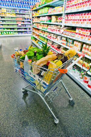 supermarket shopping: a shopping cart is in an aisle of a supermarket in the stacks