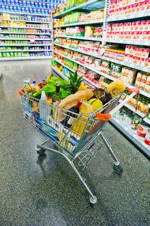 estanterias: un carrito de la compra est� en un pasillo de un supermercado en las pilas Editorial
