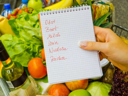 local supply: a woman holding a shopping list in a supermarket in the hand  german language  Stock Photo
