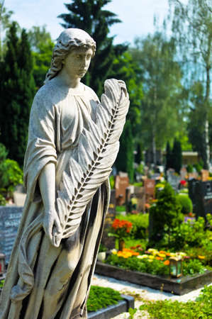 all seasons: an angel watches as a statue on the tomb in a cemetery Editorial