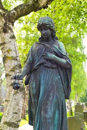 angel cemetery: an angel watches as a statue on the tomb in a cemetery Editorial