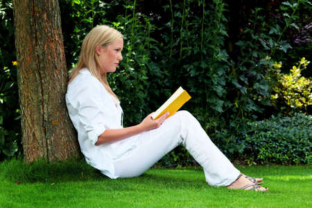 inform: a young woman sitting on the grass and reading a book  recreation in the park Stock Photo