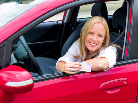 a young woman proudly displays her license  license and new car  photo