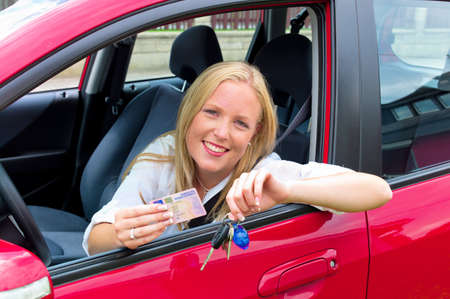 driving school: a young woman proudly displays her license  license and new car