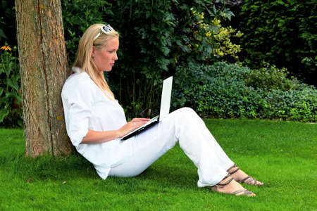 a young woman sitting with a laptop computer in the garden and surf the internet  wi-fi in the park Stock Photo - 14587373