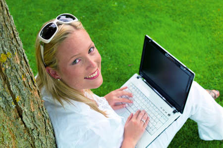 edv: a young woman sitting with a laptop computer in the garden and surf the internet  wi-fi in the park Stock Photo