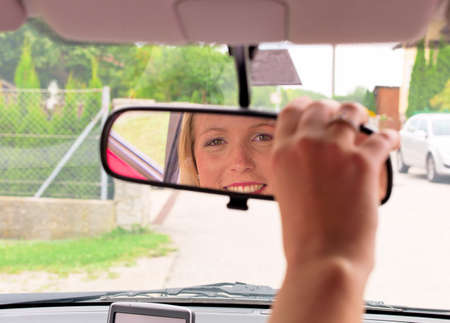 directed: a young woman directed the rearview mirror before driving their new car