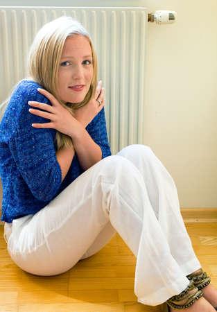 heizk�rper: Eine junge Frau sitzt vor einem Heizk�rper im Winter Raumtemperatur ist zu niedrig