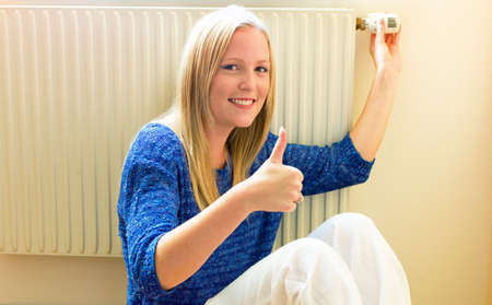 temperature controller: a young woman sits in front of a radiator in the winter  Stock Photo