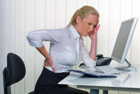 tension: a woman with back pain from long sitting in the office  health and social welfare in the workplace  Stock Photo