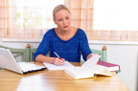 a young student in studying for her degree in her home  photo