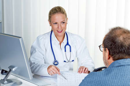 physican: a young doctor with stethoscope in her doctor s office  in an interview with a patient Stock Photo