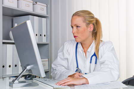 medical bills: a young doctor with stethoscope in her doctor s office  Stock Photo