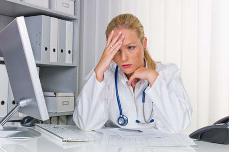doctor burnout: a young doctor with stethoscope in her doctor s office  Stock Photo