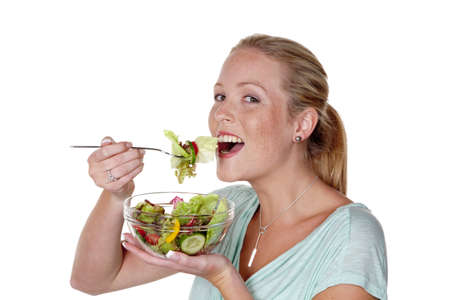 eating right: a young woman eating a fresh salad at lunch  healthy diet with vitamins