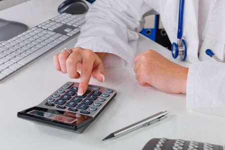 honorarios: un m�dico en el consultorio realiza los gastos administrativos de trabajo en la oficina del doctor s Foto de archivo