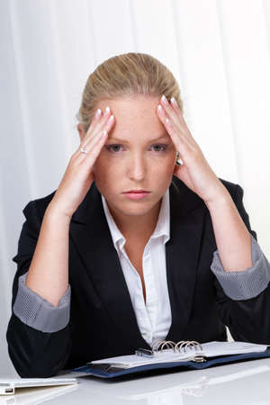 tenseness: a young woman with migraine headaches and is sitting in an office  Stock Photo