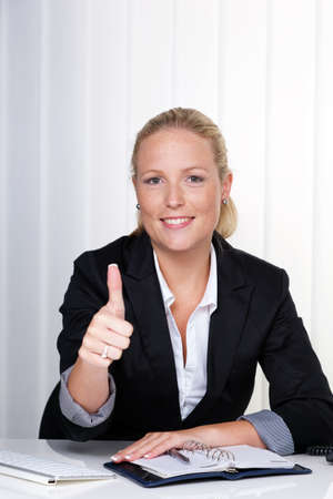 freelancers: a young successful woman sitting at her desk in the office  Stock Photo