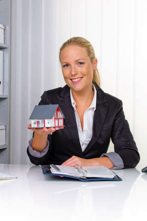 accommodation space: a young real estate agent with a model home in her office
