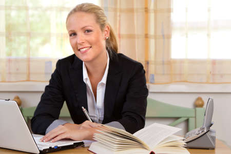 firm: successful young businesswoman at desk with laptop computer and break