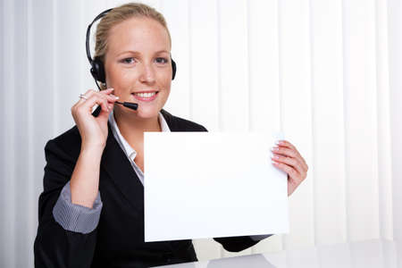 a friendly young woman with a headset on the phone with customer service to a customer  hotline staff friendly Stock Photo - 14587279