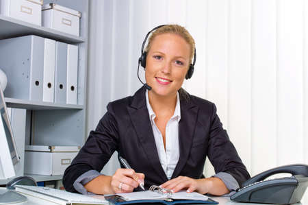 satisfied people: a friendly young woman with a headset on the phone with customer service to a customer  hotline staff friendly  Stock Photo