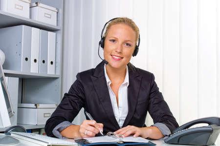 servicio al cliente: una amable mujer joven con un auricular en el tel�fono con servicio al cliente a una l�nea directa de un personal amable Foto de archivo