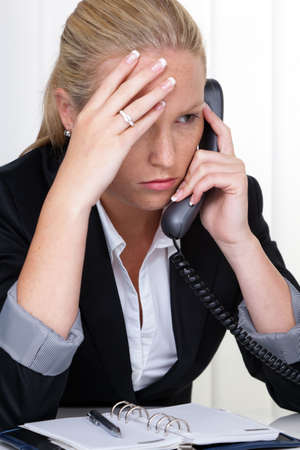revised: a frustrated woman telephoned the office  stress and strain in the workplace  Stock Photo