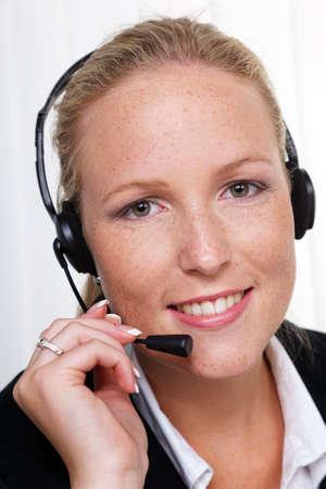 een vriendelijke jonge vrouw met een hoofdtelefoon op de telefoon met de klantenservice om een klant hotline personeel vriendelijk