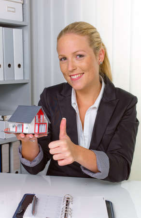 a young real estate agent with a model home in her office  Stock Photo - 14587338