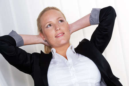 whip: a pensive business woman sitting on her chair with his hands behind his head Stock Photo