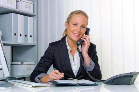 カレンダーのオフィスおよび記録の日付でフレンドリーな女性に彼女の机で電話をかけ 写真素材