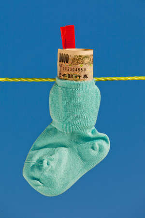 care allowance: baby socks on clothesline with yen bills from japan