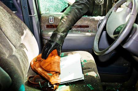 ein Dieb stahl eine Handtasche aus einem Auto durch eine zerbrochene Seitenfenster Editorial