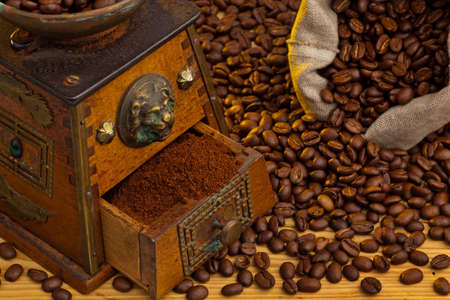 many coffee beans are next to a coffee grinder  freshly ground coffee photo
