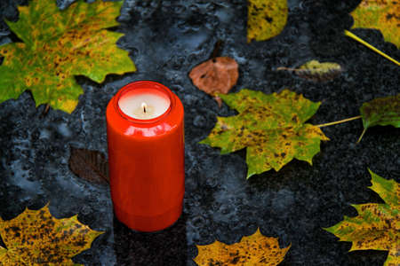 a grave light of all saints in the fall with leaves photo